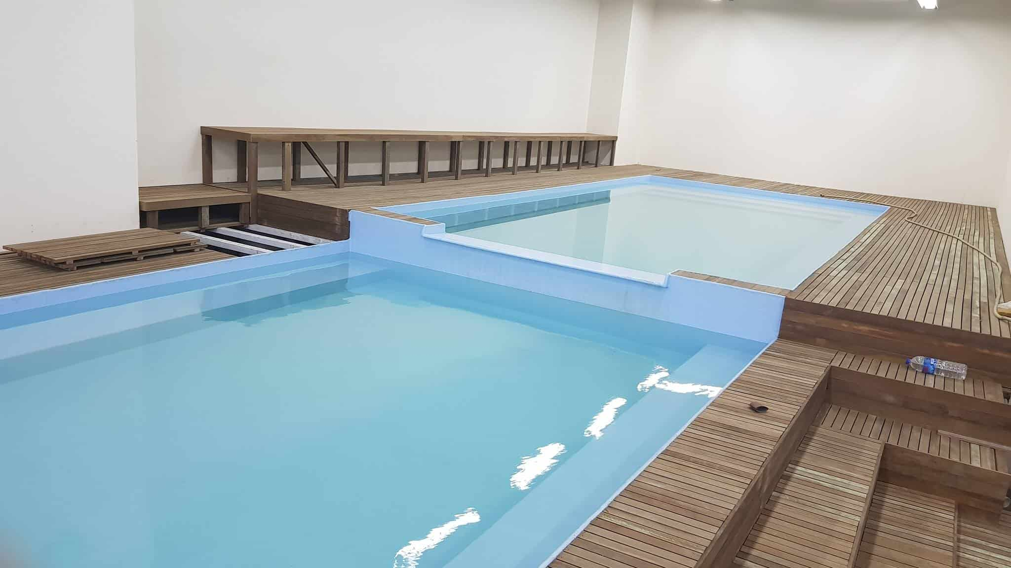 Long swimming pool at 2 different heights with seating area at the sides