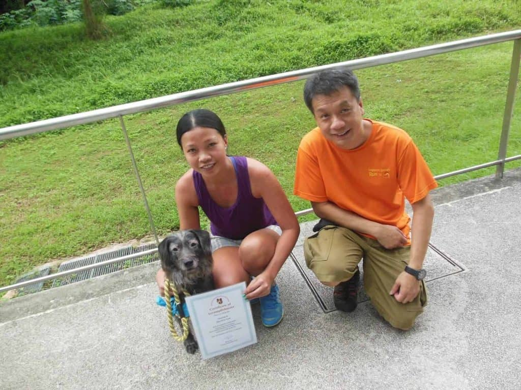 Man and woman posing with dog and woman holding a certificate