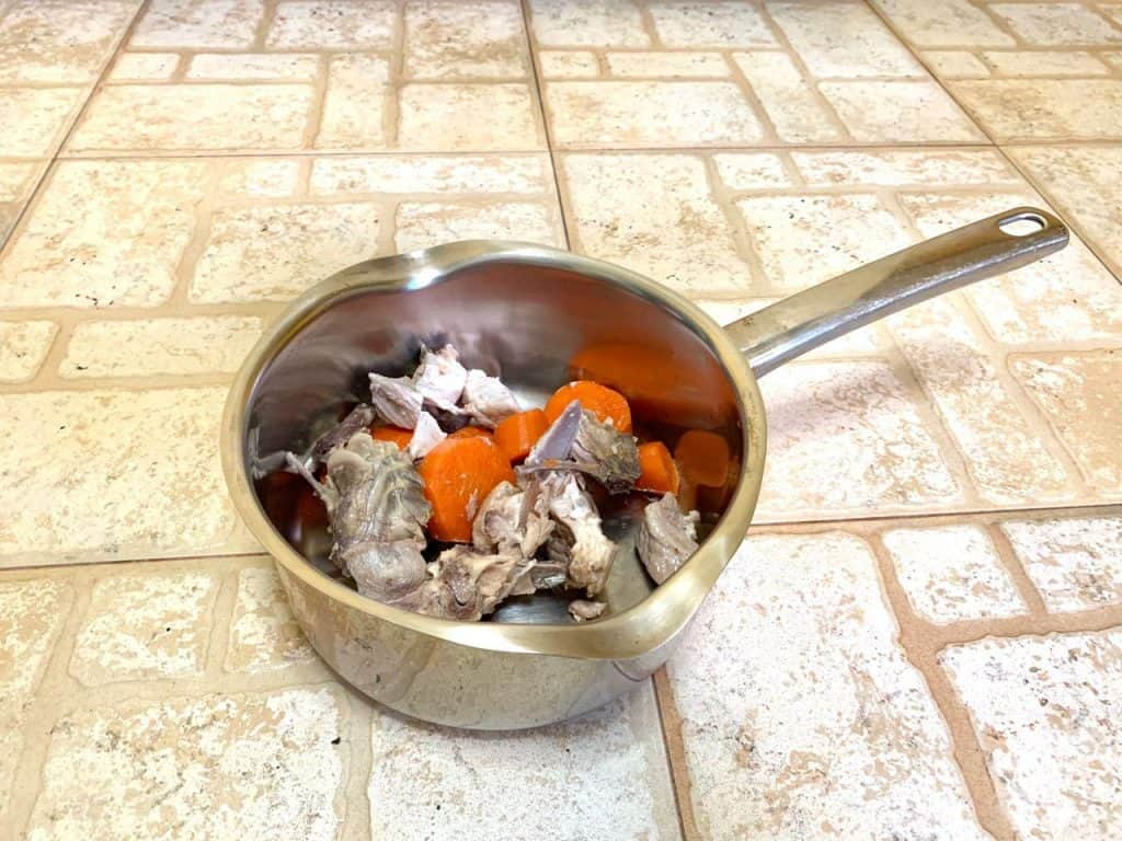 Ingredients for chicken broth inside a metal pot