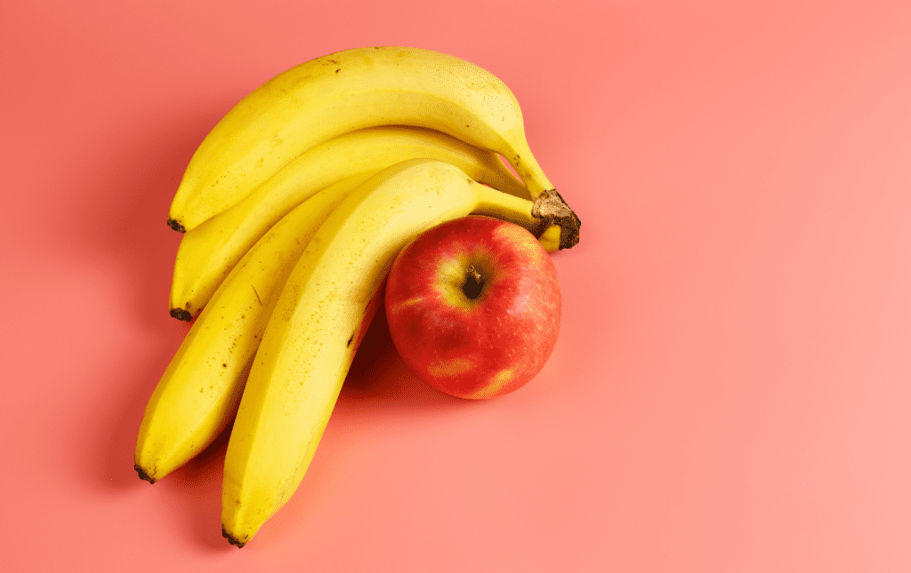 A bunch of bananas and an apple on a pink background